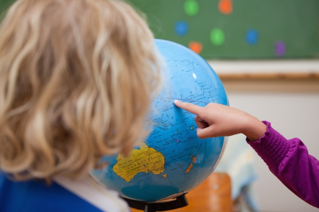 Finger of a little girl showing a country to a classmate