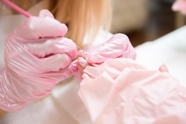 指の爪の治療、ブラシとラッカーでの塗装。安全フェイスマスクのプロのマニキュアマスター。
