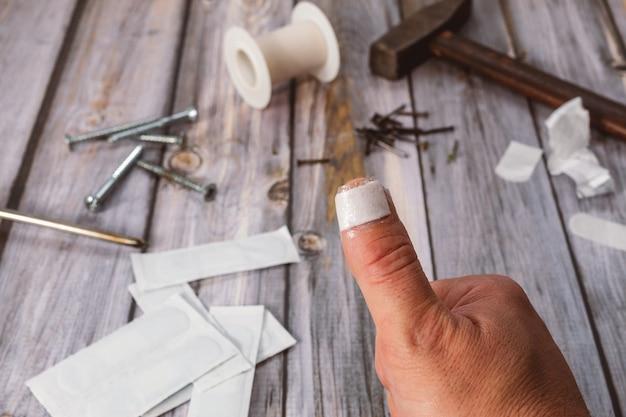 부상 후 파란색 반창고를 가진 백인 남자의 손가락