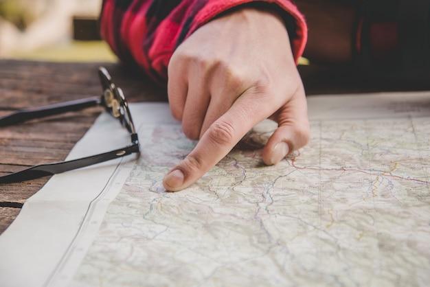 Палец, указывающий местоположение на карте крупным планом