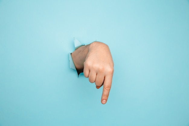Finger pointing down through torn blue paper wall. hand gestures of direction.