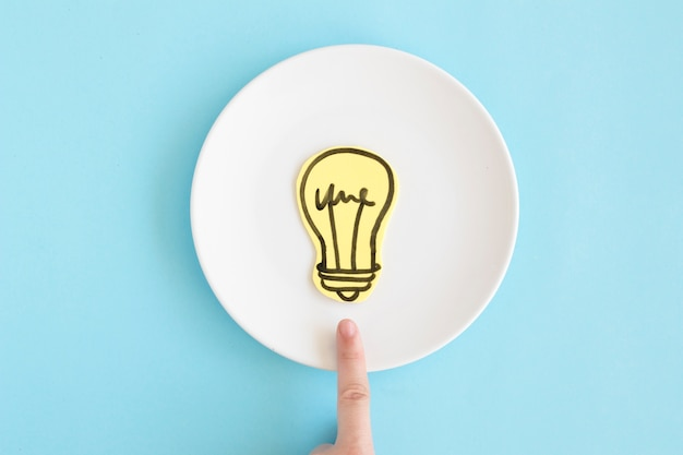 Barretta che indica verso la lampadina di carta del ritaglio sul piatto bianco contro fondo blu