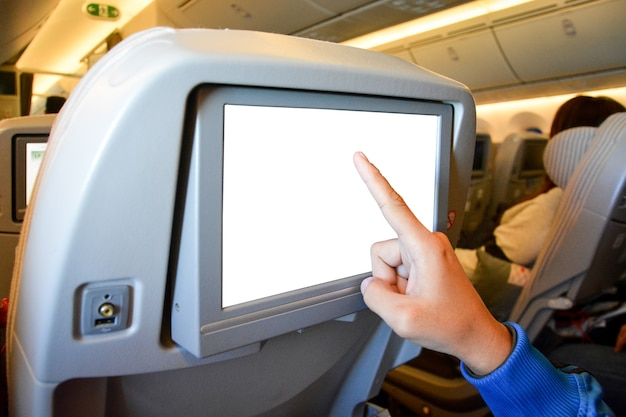 Finger pointing to white blank lcd screen monitor behind passenger seat on the airplane