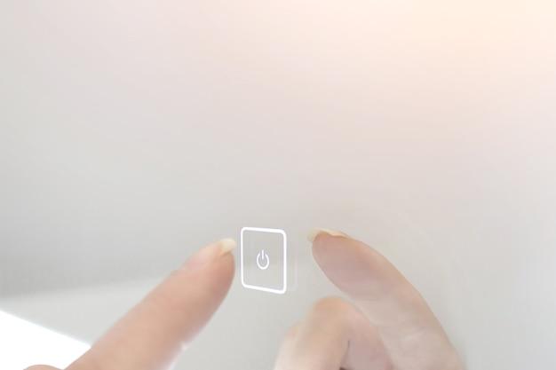 Finger press power button on screen, modern technology concept.