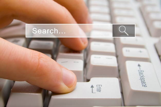 Finger presses the computer key enter with search bar