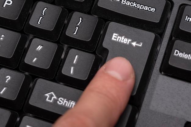 Finger presses the enter button. black keyboard close up.