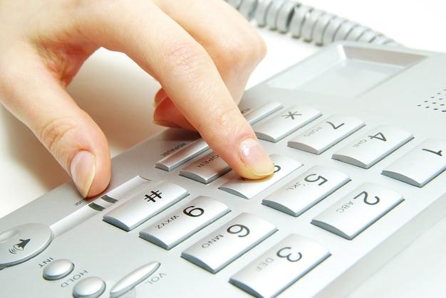 灰色の電話で指が図を押す