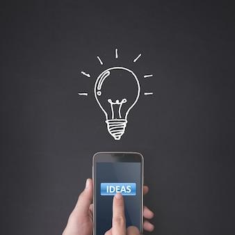 アイデアのコンセプトを持つスマートフォンを押す指