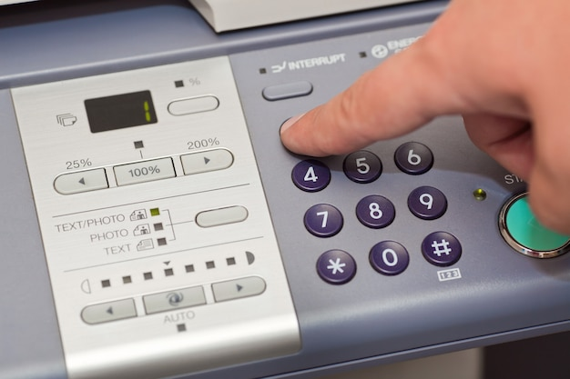 Finger pressing the buttons of the copier