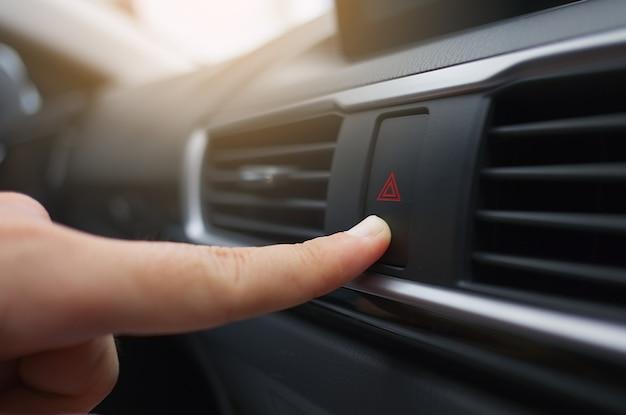 Finger pressing emergency button on car dashboard.