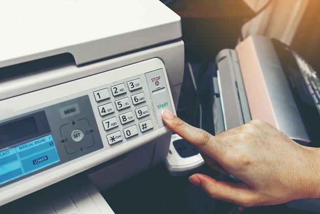 Finger pressing start button of fax machine