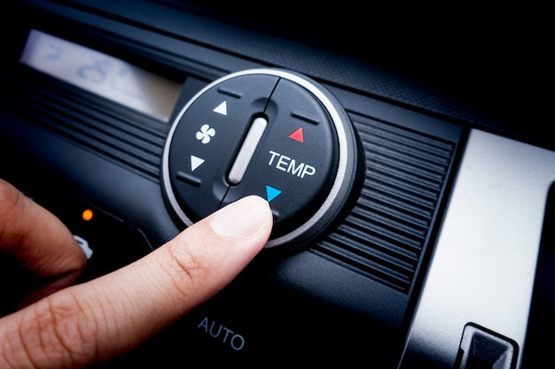 Finger pressing on temperature switch of a car air conditioning system