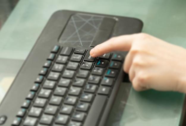 コピースペース付きガラストップテーブルのワイヤレスbluetoothキーボードの指押しエンターキーボタン