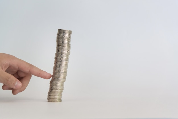 Finger pushing a pile of coins
