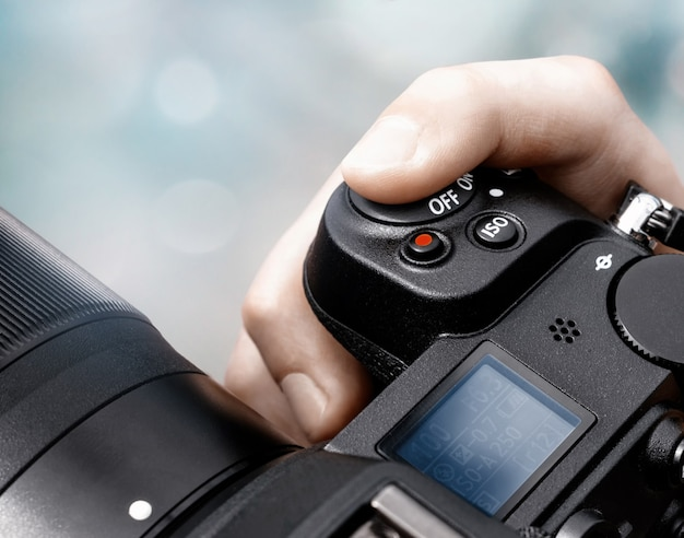 Finger pushing shutter button on a slr camera close-up on a blurred abstract background.