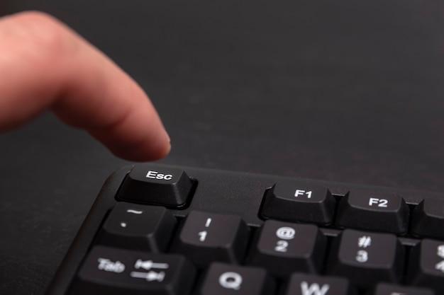 Esc 버튼에 손가락이 닿습니다. 검은 색 키보드 이스케이프 키. 확대