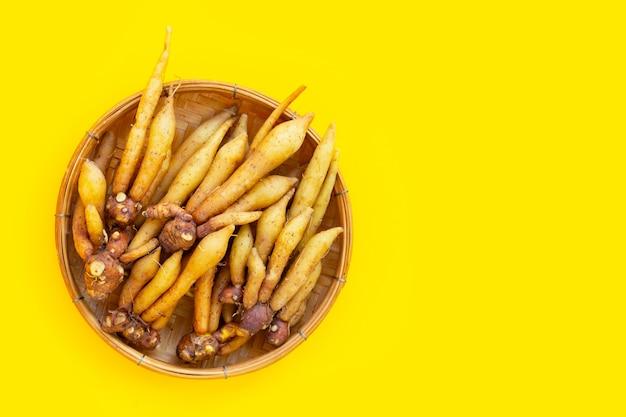 노란색 배경에 대나무 바구니에 손가락 루트입니다.