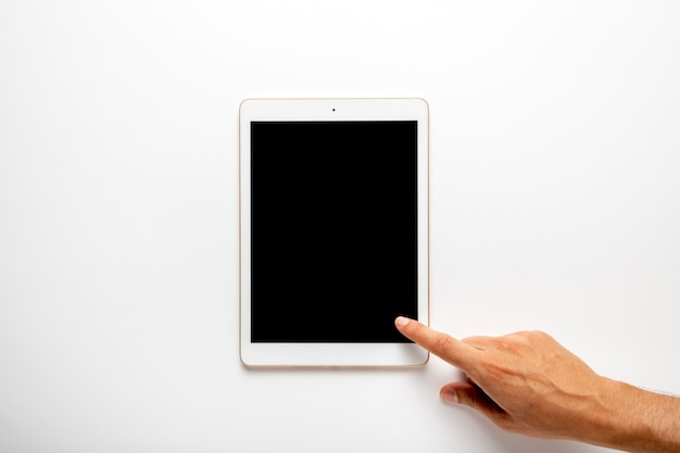 Палец, касающийся плоского экрана планшета