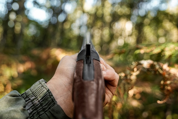 Finger on the trigger of a hunting rifle in the autumn forest