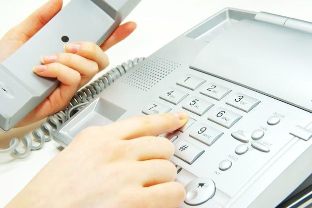青い電話のキーパッド付きの指