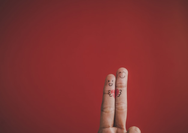Finger with emotion on red background