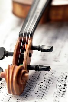 指板と楽譜の上にペグが横たわっているバイオリンのカールがクローズアップ