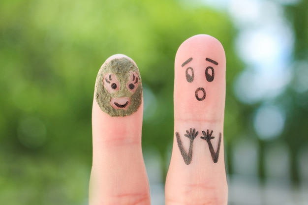 Fingers art of couple. husband saw his wife with clay face mask and was afraid.