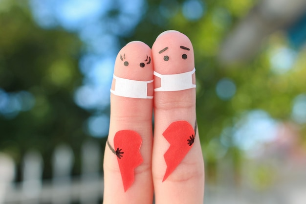 Fingers art of couple in medical mask from covid-2019. concept of couple holding broken heart.