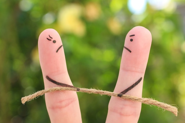 Fingers art of couple. they playing tug of war with rope.