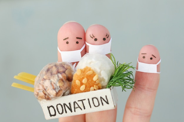 Fingers art of couple with face mask holding donation box with food