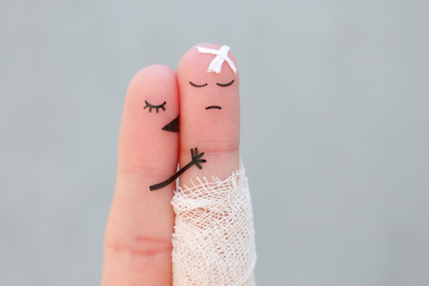 Fingers art of displeased couple. man is sick, woman feels sorry for him. she kisses and hugs his.