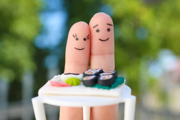 Fingers art of happy couple. man and woman eat sushi in cafe.