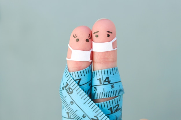 Fingers art of happy couple with tape measure. concept of sports people in medical mask from covid-2019.