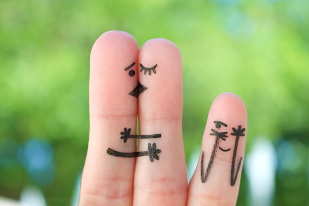 Fingers art of happy family. concept of couple kisses,  child spies on them.