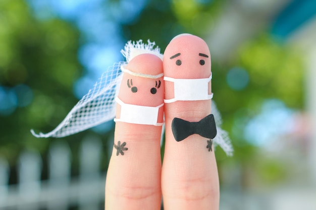 Fingers art of happy newlyweds in medical mask