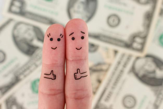 행복한 커플의 손가락 예술. 남자와 여자는 돈의 배경에 클래스의 표시를 보여줍니다.