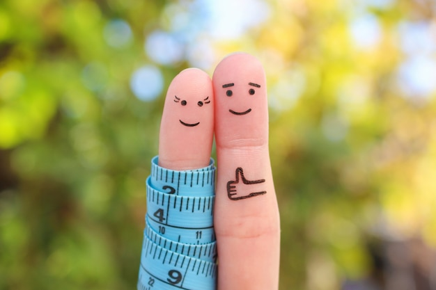 Искусство пальцев счастливой пары с рулеткой. концепция похудения вместе.