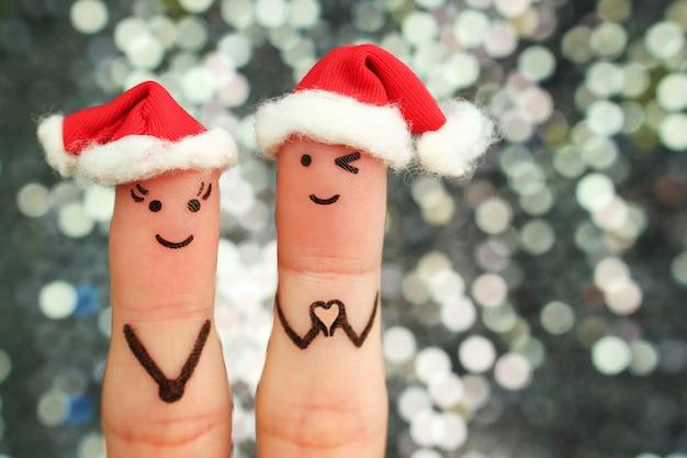 Искусство пальцев пары празднует рождество. концепция мужчины и женщины, смеясь в новогодних шапках. парень показывает пальцы в форме сердца.