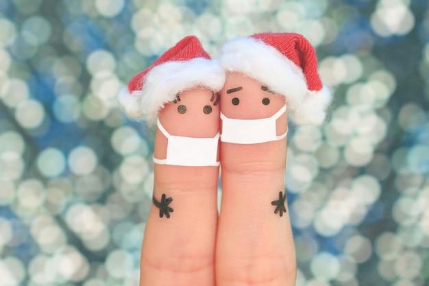 Искусство пальцами пары в медицинской маске от covid-2019 празднует рождество.