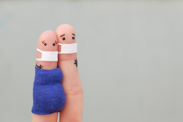 Covid-2019からの医療マスクのカップルの指の芸術。女性は妊娠しています。