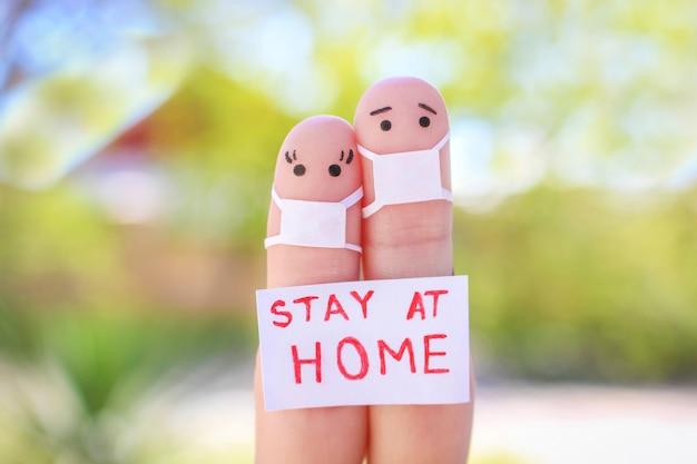 Пальцы искусство пары с маской сидит в карантине дома. люди держат плакаты дома, чтобы защитить себя от covid-2019.