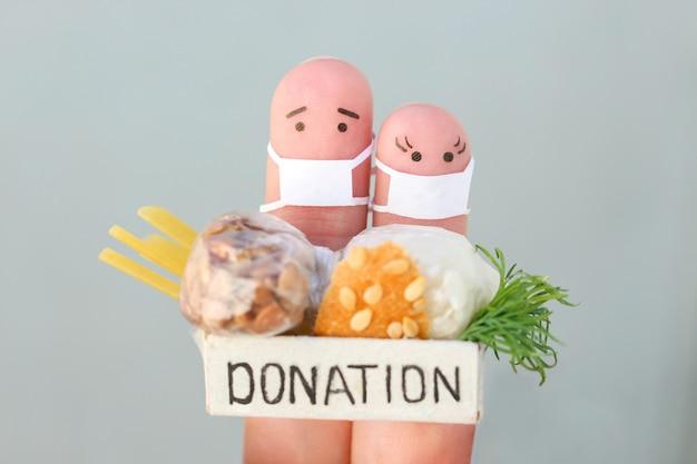 フェイスマスクとカップルの指アート。食べ物と募金箱を保持している男性と女性。