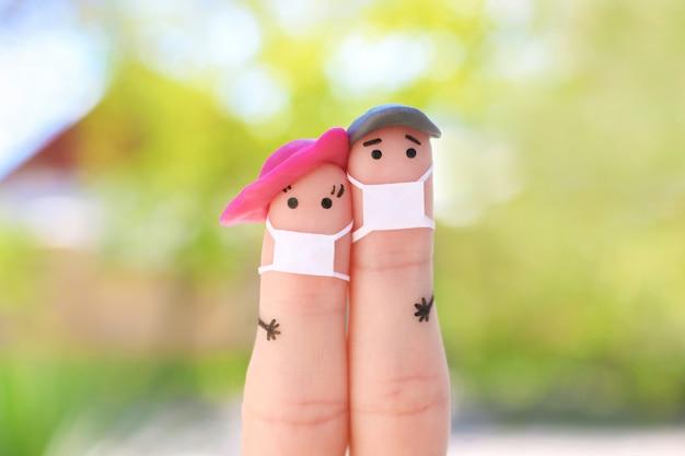 徒歩でフェイスマスクが付いているカップルの指アート。