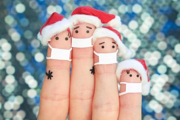 Пальцы искусства семьи в медицинской маске от covid-2019 празднуют рождество.