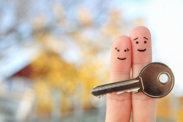 Пальцы искусство счастливой пары. семья держит ключ от дома.