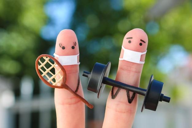 Искусство пальцев счастливой пары в медицинской маске от covid-2019. понятие семьи в спорте.