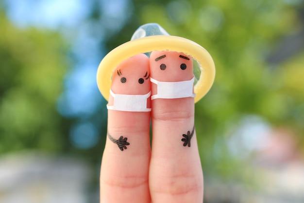 Covid-2019에서 의료용 마스크를 쓴 행복한 커플의 손가락 예술. 안전한 섹스의 개념입니다.