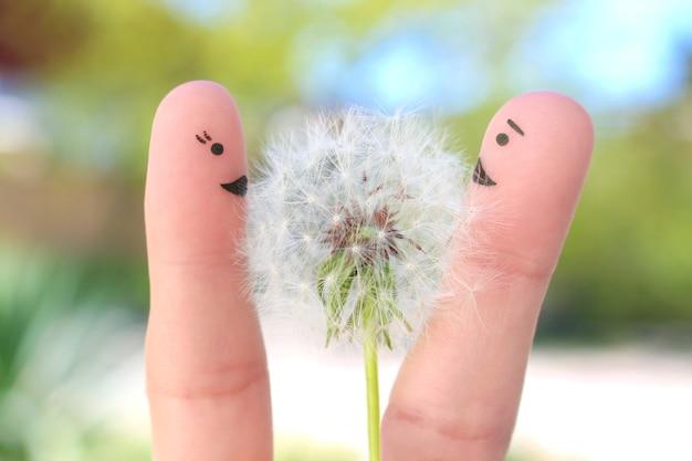 Пальцы искусство счастливой пары. мужчина дарит цветы женщине.