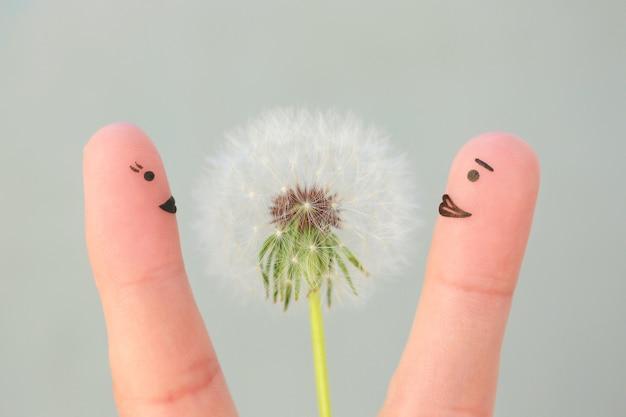 幸せなカップルの指アート。男性は女性に花をあげています。