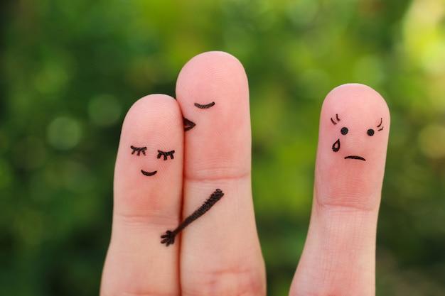 Искусство пальцев счастливой пары. мужчина целует женщину в щеку. девушка ревнует и злится.